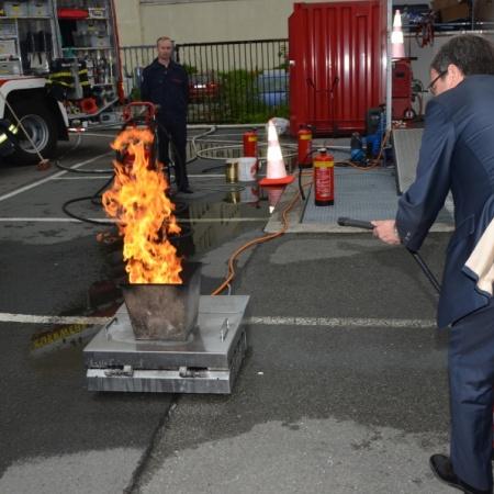 Mit dem Feuerlöscher in der Hand erprobt sich Armin Laschet unter fachkundiger Anleitung dabei, ein kleines Feuer zu löschen.